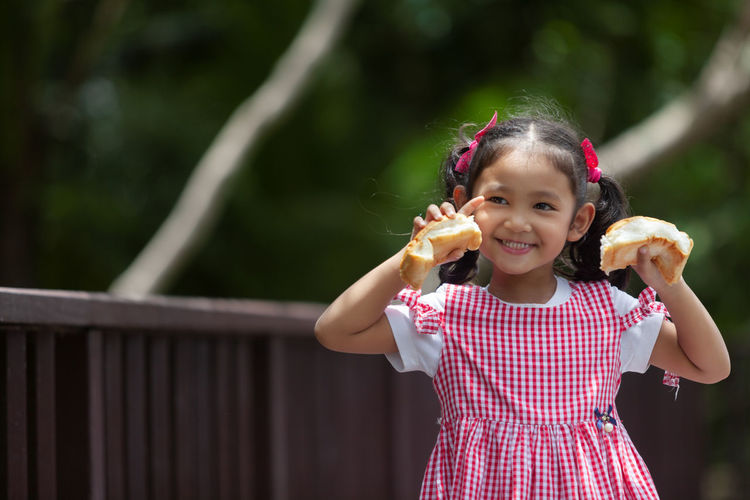 Portrait of smiling girl holding bread outdoors