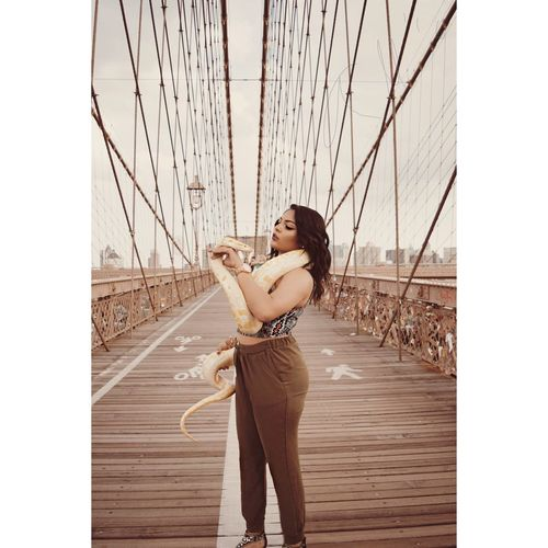 Young woman holding snake on brooklyn bridge