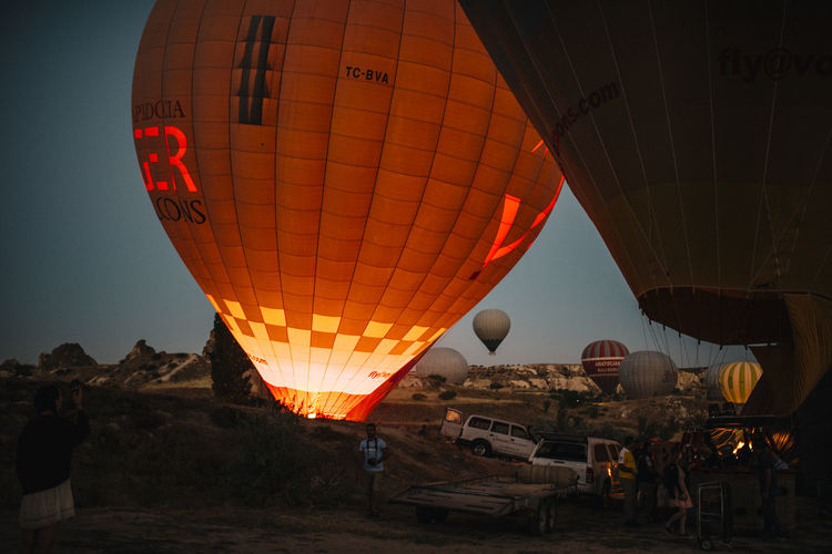 Air Vehicle Hot Air Balloon Balloon Incidental People Mode Of Transportation Transportation Nature Ballooning Festival Sky Adventure Real People Burning Fire Travel Leisure Activity Outdoors People Orange Color Illuminated Flying