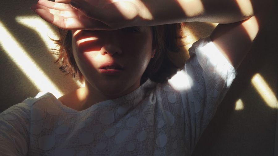 Portrait Of Boy Shielding Himself From Sunlight At Home