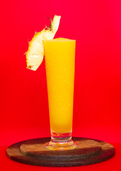 Yellow pineapple smoothie with fresh pineapple on glass with red background,healthy detox or diet concept Glass Drinking Glass Food And Drink Refreshment Colored Background Alcohol Drink Household Equipment Studio Shot Indoors  Yellow Food No People Red Red Background Freshness Fruit Cocktail Healthy Eating Close-up Orange Background