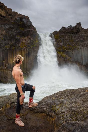 Full length of shirtless man standing on rock