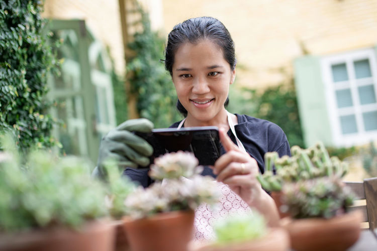 Portrait of smiling woman photographing plant in back yard