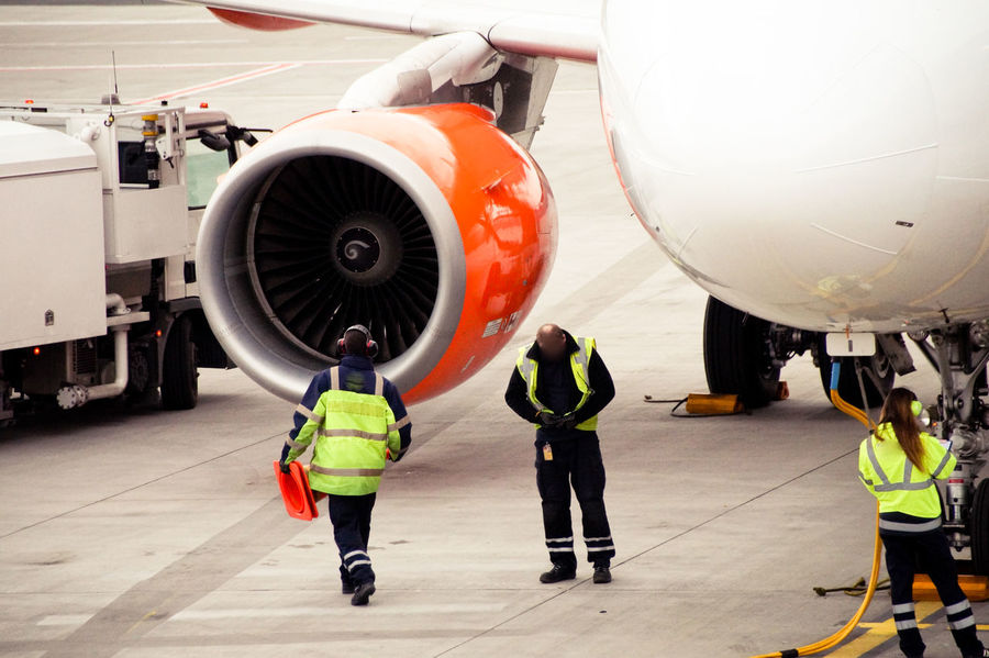 Aerospace Industry Air Vehicle Airplane Airplane Hangar Airplane Mechanic Airport Airport Runway Art Is Everywhere Break The Mold Commercial Airplane Day Engineer Full Length Industry Jet Engine Mechanic Men Outdoors Protective Workwear Reflective Clothing Repairing Safety Standing TCPM Transportation
