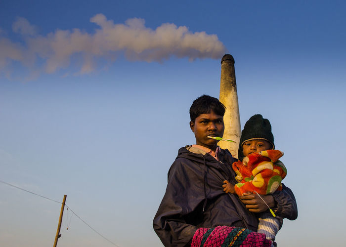 Father carrying daughter while standing against chimney and sky during sunset