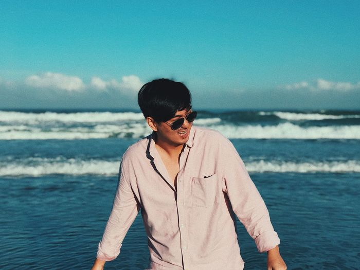 Man wearing sunglasses standing by sea against sky