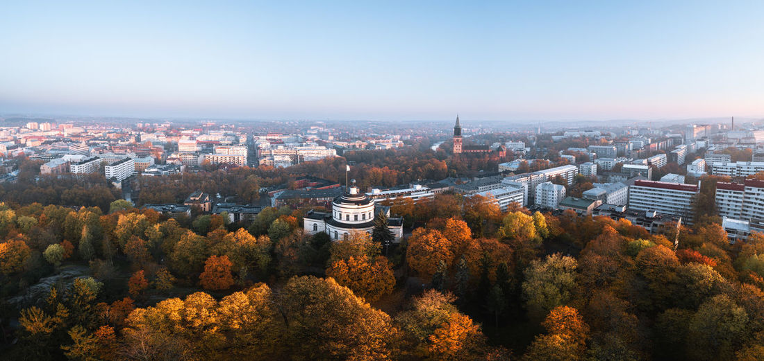 High angle view of trees and buildings against sky during autumn