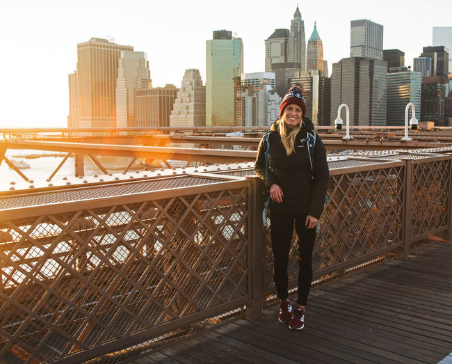 Young female on Brooklyn Bridge with sun setting behind downtown Manhattan sky scrapers New York New York City Architecture Big Apple Building Exterior Built Structure Casual Clothing City City Life Cityscape Day Front View Full Length Leisure Activity Lifestyles Looking At Camera Modern One Person Outdoors Portrait Railing Real People Sky Skyscraper Standing Urban Skyline Young Adult Young Women