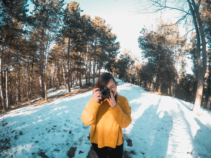 Woman photographing on snow covered tree
