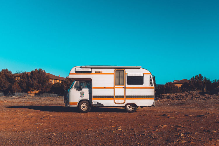 Arid Climate Blue Campervan Car Clear Sky Copy Space Day Environment Land Land Vehicle Landscape Mode Of Transportation Motor Vehicle Nature No People Off-road Vehicle Outdoors Road Sky Transportation Travel Truck Van - Vehicle