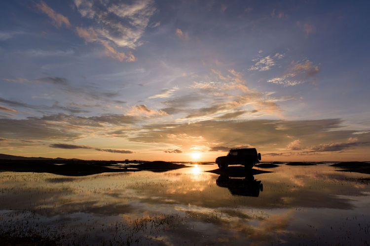 Silhouette Sport Utility Vehicle Reflecting On Lake During Sunset