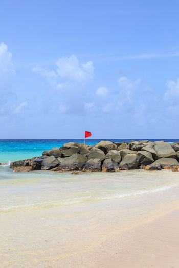 A Warning Flag on a Beach Barbados Red Beach Beauty In Nature Blue Cloud - Sky Day Groyne Horizon Over Water Nature No People Outdoors Red Flag Rock - Object Rocks Scenics Sea Sky Tranquil Scene Tranquility Warning Warning Flag Water