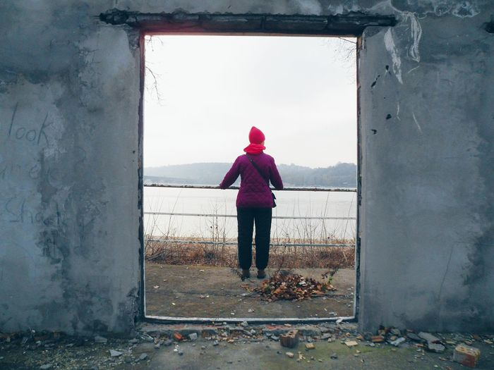 Rear view of woman standing by window against sky
