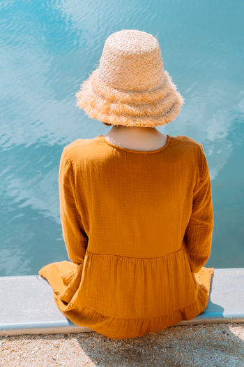 From behind woman resting on the beach. girl in straw hat enjoying beautiful view. photos from back