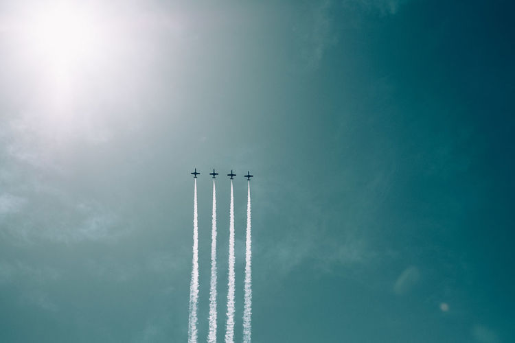 Low angle view of airplanes flying against blue sky