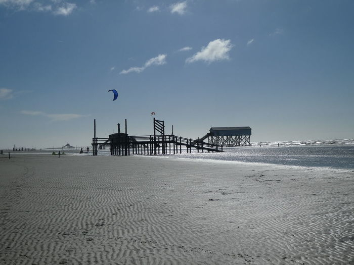 North Sea Blue Sky And Clouds Kite Surfer Beach Sunshine Reflection On Water Stilt Houses Stilt House Water Built Structure Scenics - Nature Architecture Sand Tranquility Beauty In Nature Tranquil Scene Sea Building Exterior
