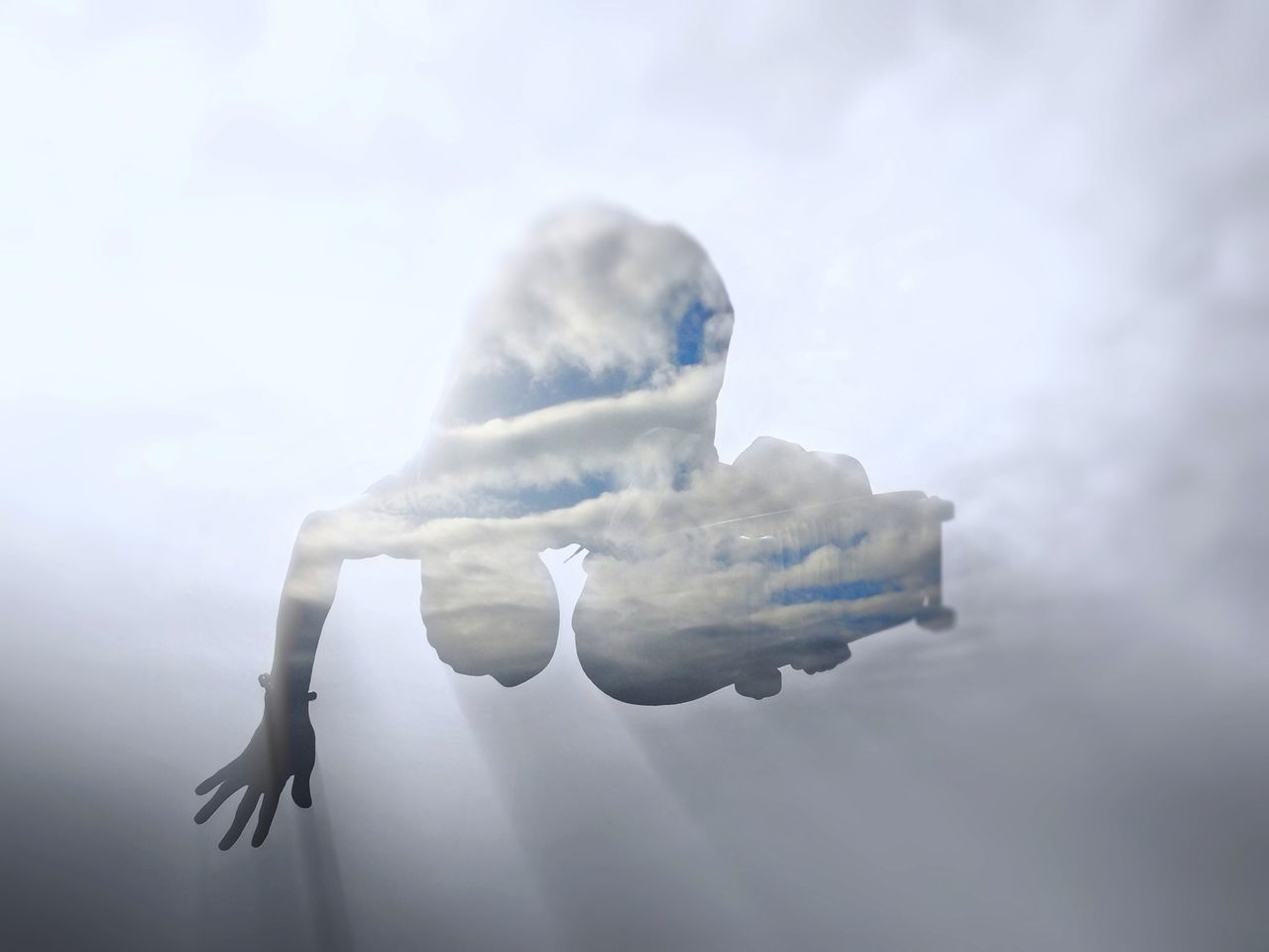 Double exposure of person jumping with skate board against cloudy sky