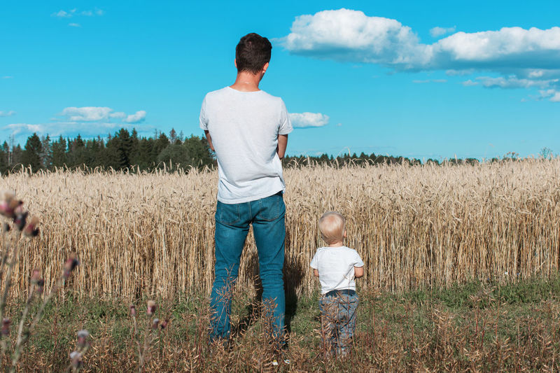 Father and son Adult Agriculture Beauty In Nature Casual Clothing Cereal Plant Childhood Cloud - Sky Day Family Father Field Full Length Grass Growth Leisure Activity Lifestyles Men Nature Outdoors Real People Rear View Sky Standing Togetherness Two People EyeEmNewHere This Is Masculinity