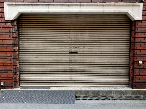 garage in Osaka. Japanese design influences building construction. Doorway Door Gritty Japanese Culture Travel Still Life Urban Scene Corrugated Iron Industry Store Textured  Shutter Brick Wall Closed Architecture Weathered Garage Corrugated