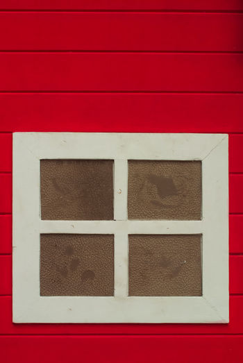 Full frame shot of window on red wall