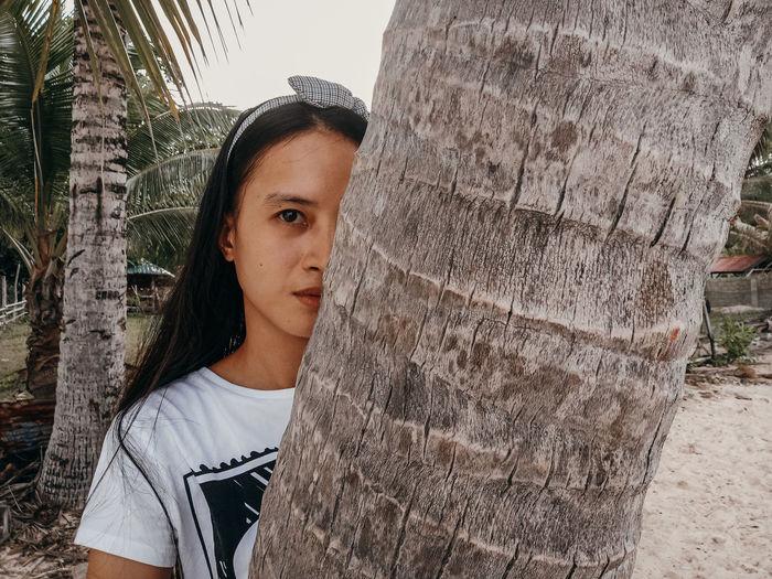 Portrait of teenage girl standing by tree trunk