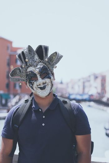 Portrait Of Man Wearing Venetian Mask While Standing Against Sky