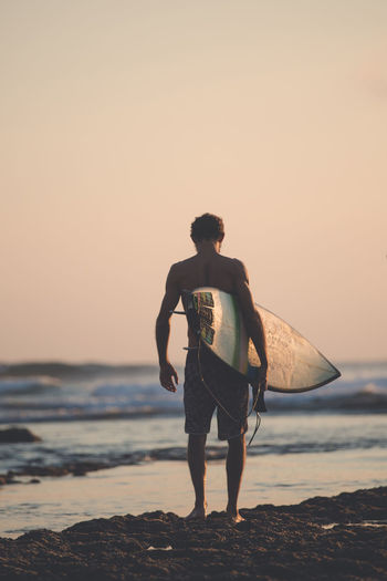 Rear view of man with surfboard standing at beach against clear sky during sunset
