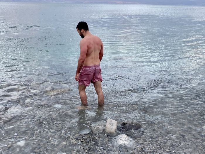 Full length of shirtless man standing in sea