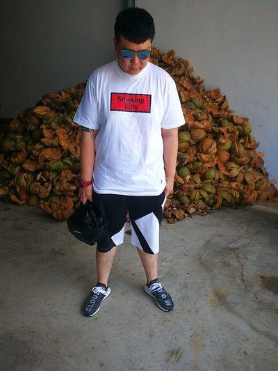 Man In Sunglasses Standing Against Heaped Coconut Peel