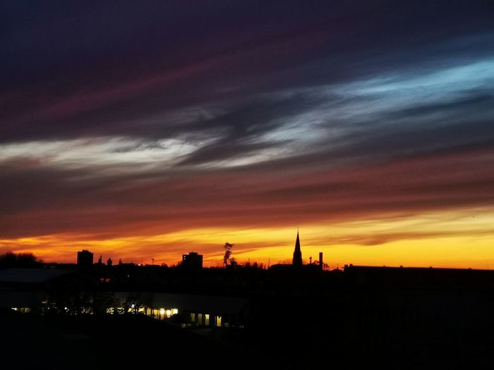 Silhouette of city against dramatic sky during sunset