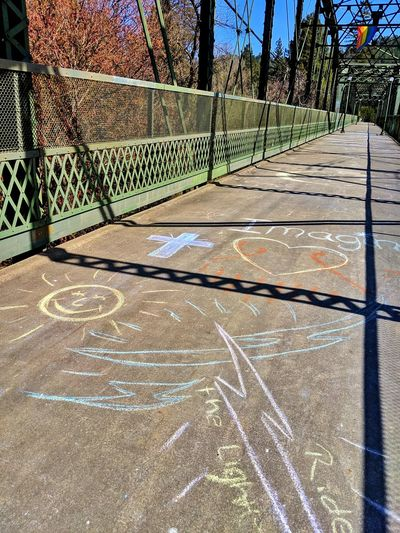 Street art. Inspiration after the flood. Street Art Chalk Art Inspiration Bridge Cable Struts Colorful Sunshine SMILY FACE Cross Green Shadow Therapeutic Caring Walkway Golden Asphalt Black Floid Aftermath Sunlight Shadow Sky Chainlink Fence Chainlink Love Lock Metal Wire Mesh Metal Grate Rusty