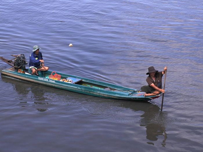High angle view of men sitting on boat in river