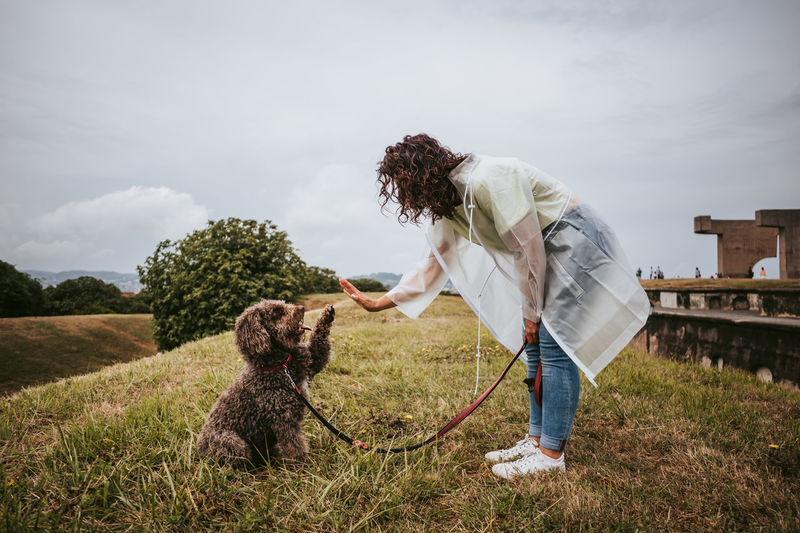 Woman with dog standing on grass against sky