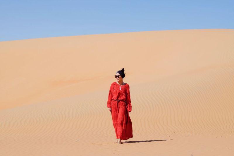 Full Length Of Woman Walking On Sand Dune In Desert Against Clear Sky