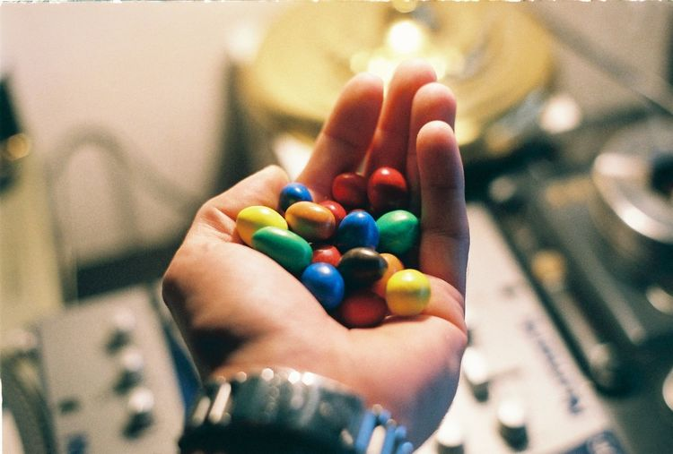 Cropped hand of man holding colorful candies