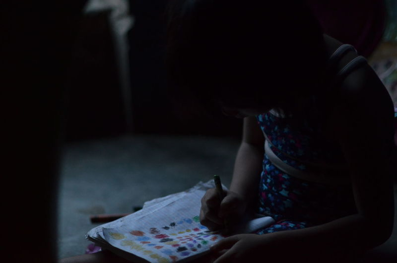 Girl Coloring On Book While Sitting In Darkroom