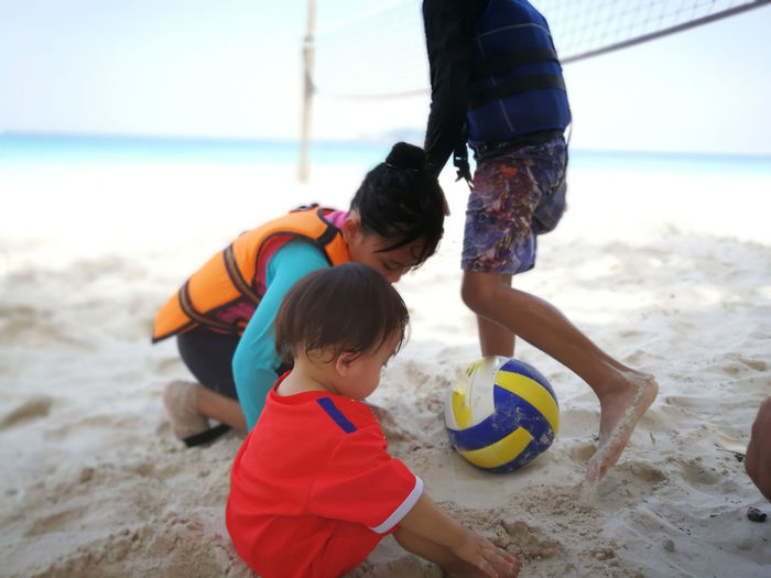 Boy with sisters playing volleyball at beach
