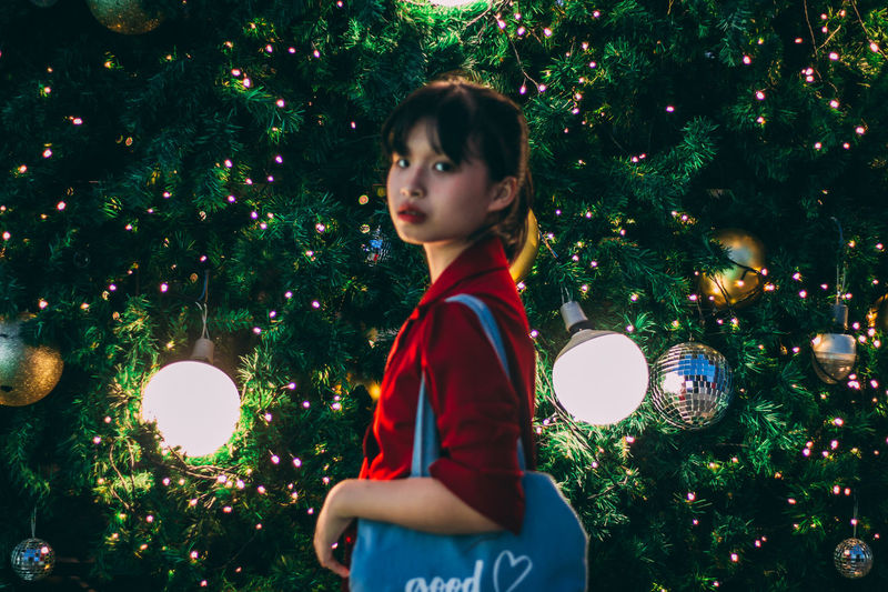 Portrait of woman standing against illuminated christmas tree at night