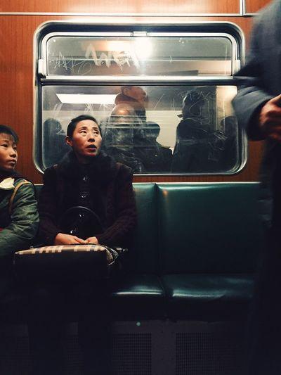 Woman sitting in illuminated mirror
