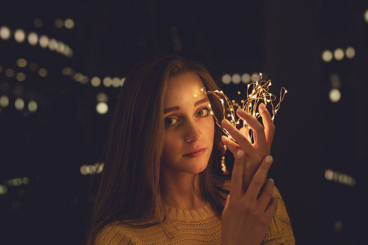Portrait Of Young Woman Holding Illuminated String Lights In Darkroom