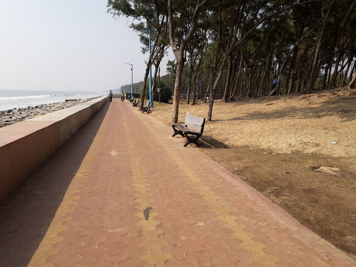 Empty benches on footpath by sea against sky