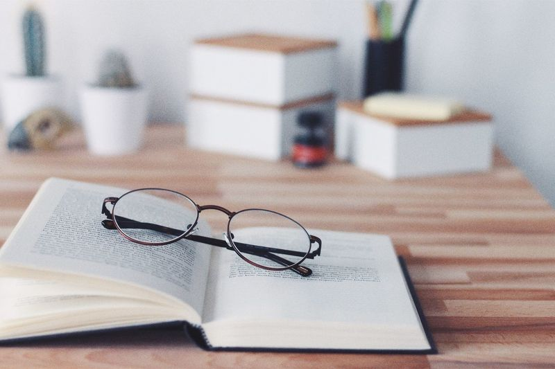 Close-up of book with eyeglasses on table