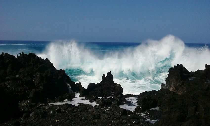 Wave Splashing At Rocky Shore Against Sky