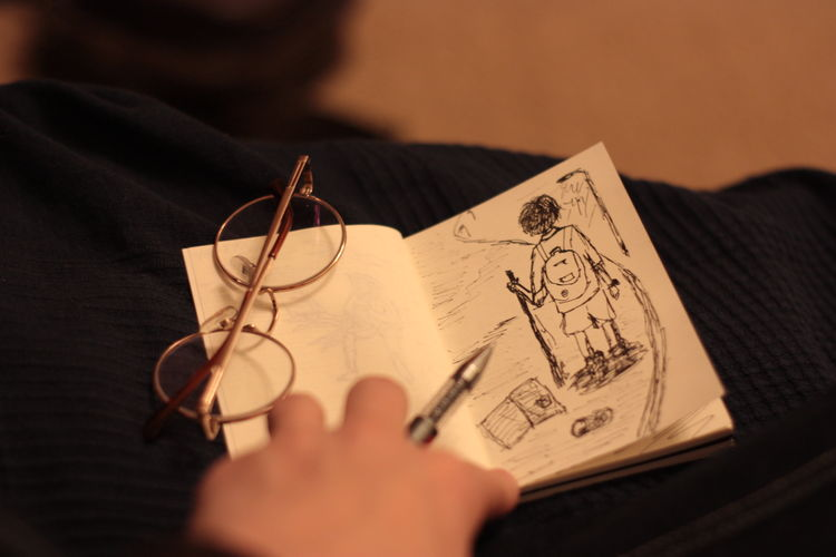 Close-Up Of Sketch On Book With Eyeglasses On Table