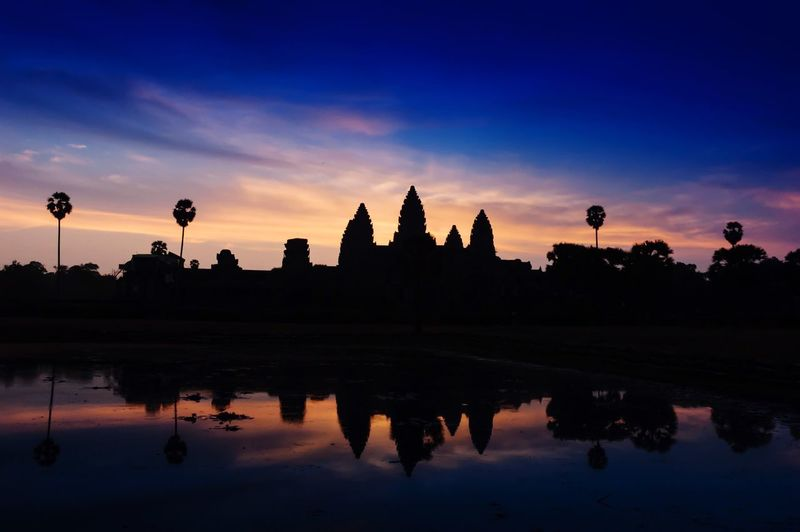 Reflection of silhouette angkor wat temple on lake at sunset