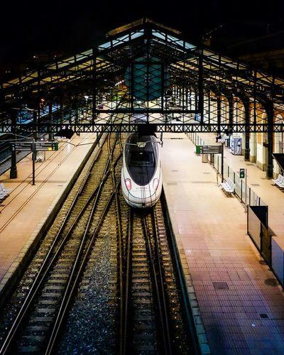 Train on railroad station platform at night
