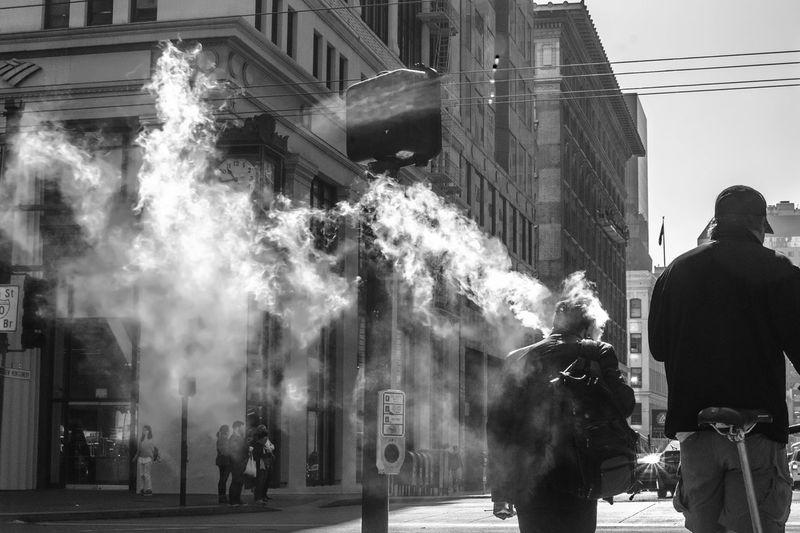 Rear view of people walking by smoke on street in city