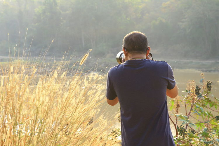 Rear view of man photographing while standing amidst plants by lake
