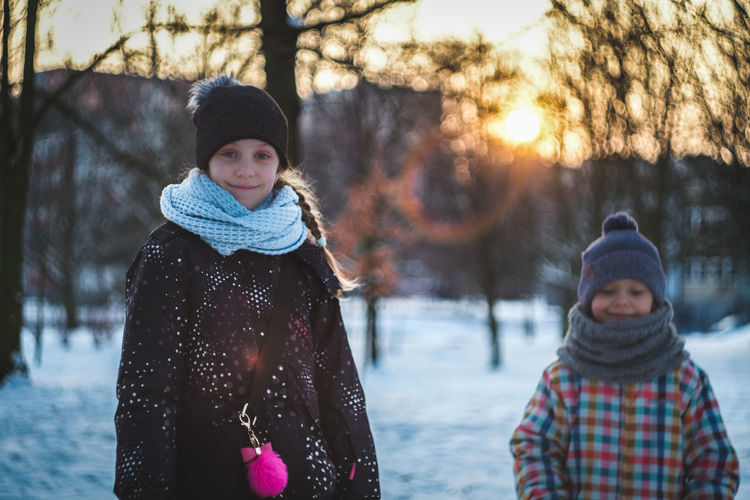 Portrait of smiling sibling standing in snow