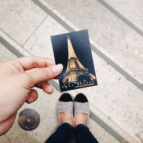 Low section of woman holding photograph with eiffel tower